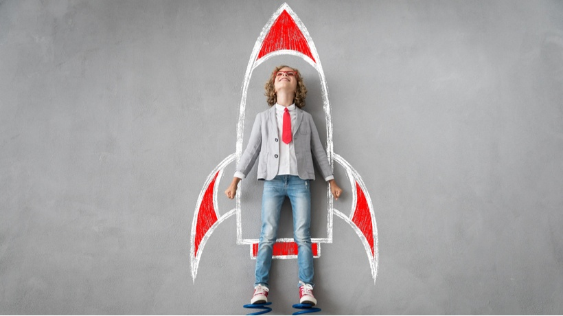 boy thinking about future standing besides rocket drawing - CollegeMarker